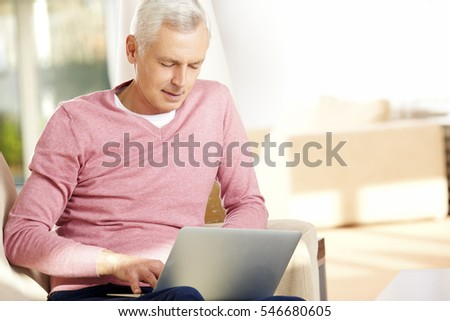Shot of a positive senior man using his laptop while sitting at home on the couch.