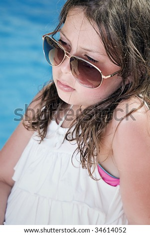 Shot of a Pretty Child in Sunglasses Sitting Next to the Pool - stock photo