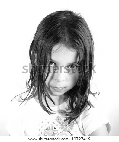 Shot of a pretty seven year old girl looking directly at the camera with her head lowered - stock photo