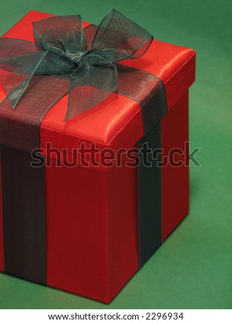 Shot of a red gift box with a green ribbon against a green background.