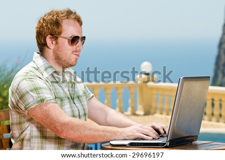 Shot of a Red Headed Male using his Laptop by the Pool - stock photo