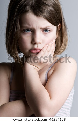 Shot of a Sad Looking Child against a Grey Background - stock photo