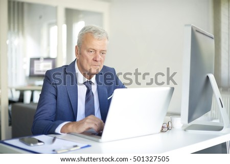 Shot of a senior bank manager using his laptop while working at office.