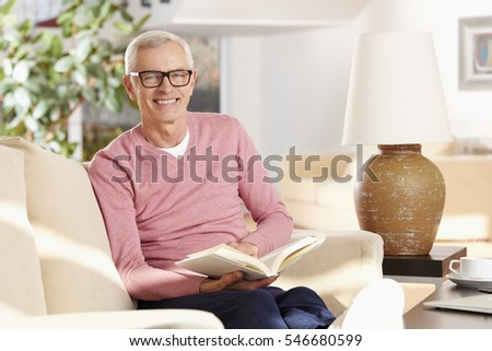 Shot of a senior man sitting on couch and reading book while relaxing at home.