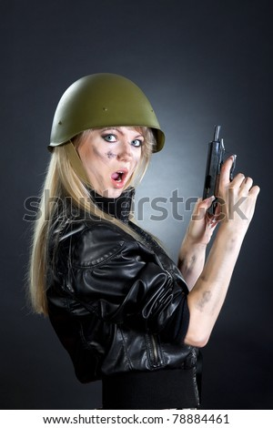 Shot of a sexy fashion style attractive woman portrait with gun in military uniform, wearing black leather jacket, posing against black background with make up. - stock photo