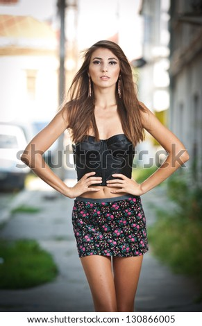 Shot of a sexy high fashion woman posing outdoor. Cute brunette with short skirt posing on a city street. Urban fashion shot - stock photo