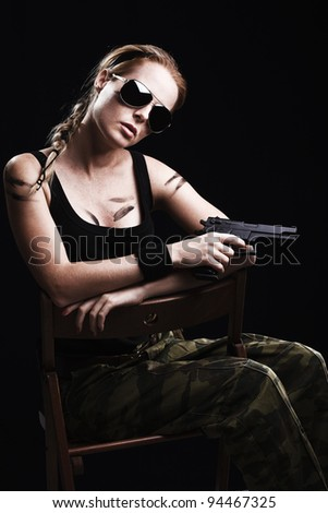 Shot of a sexy military woman posing with gun - stock photo