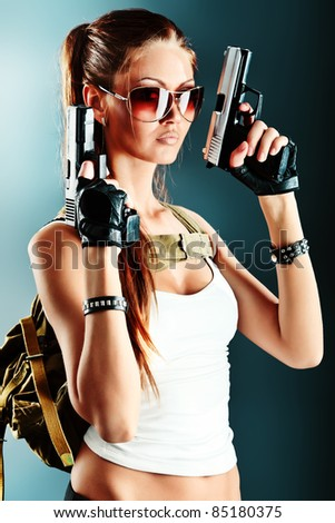 Shot of a sexy military woman posing with guns.