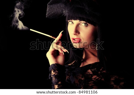 Shot of a sexy smoking woman in erotic lingerie over black background. - stock photo