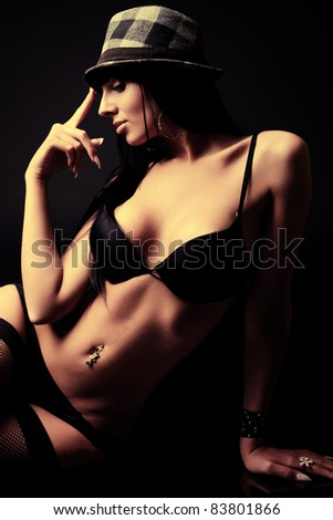 Shot of a sexy woman in black lingerie over dark background.