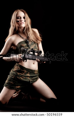 Shot of a sexy woman in military uniform posing against black background. - stock photo