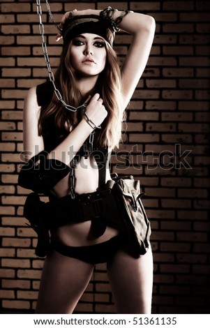 Shot of a sexy woman in military uniform posing against brick background. - stock photo