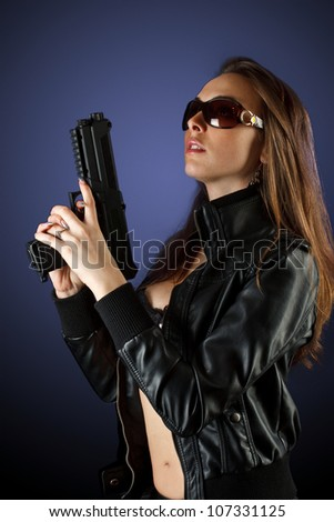 Shot of a sexy woman posing with gun in sunglass - stock photo