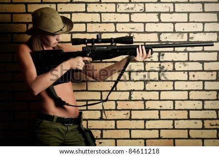 Shot of a sexy woman soldier posing against brick wall. - stock photo