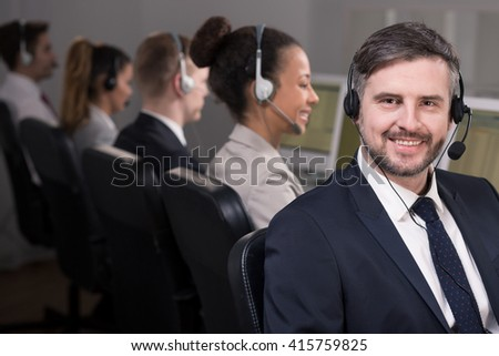 Shot of a smiling call center agent and his colleagues working in the background