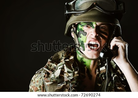 Shot of a soldier talking by radio station. Studio shot over black background.