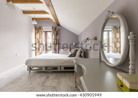 Shot of a spacious bedroom with a king-size bed and a mirror