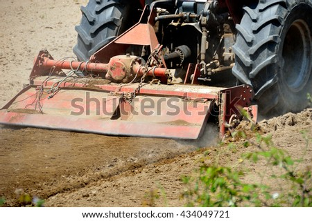 Shot of a tractor pulling a seeder over a plowed field in the late noon - stock photo