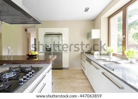 Shot of a white spacious kitchen in a modern house