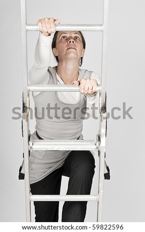 Shot of a Woman Climbing a Ladder against a Grey Background - stock photo