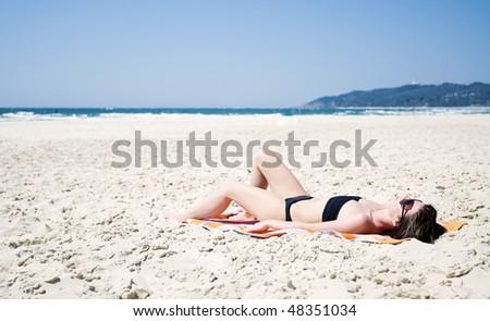 Shot of a Woman Sunbathing on the Beach at Byron Bay, Australia - stock photo