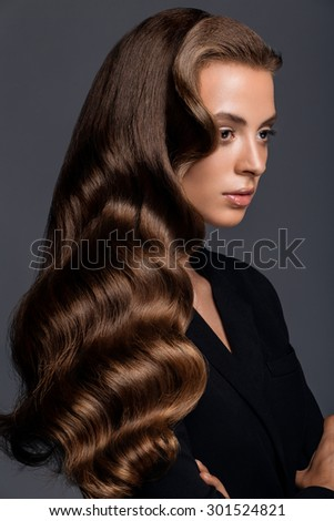 Shot of a woman with long glossy curly hairstyle in studio