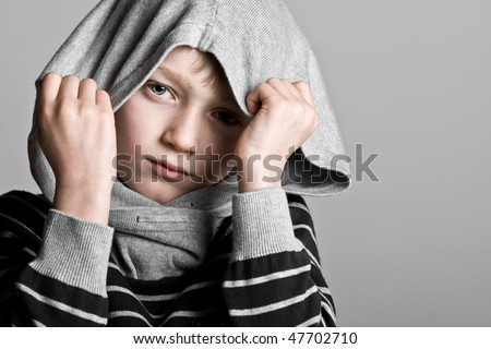 Shot of a Young Blonde Boy Hiding his Face in Hooded Top - stock photo