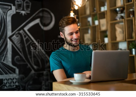 Shot of a young businessman working on his laptop in a cafe shop. Selective focus. - stock photo