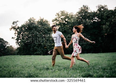Shot of a young couple holding hands and running through the park. Blurry movement, soft focus - stock photo