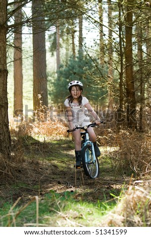 Shot of a Young Girl Riding her Bike in the Forest - stock photo