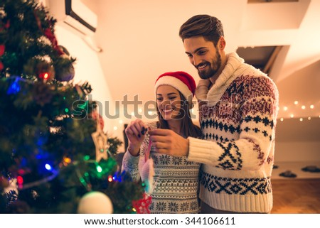 Shot of a young happy couple decorating a Christmas tree. Natural light, selective focus - stock photo