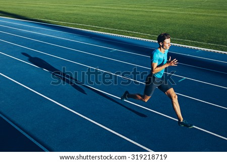 Shot of a young male athlete training on a race track. Sprinter running on athletics tracks. - stock photo