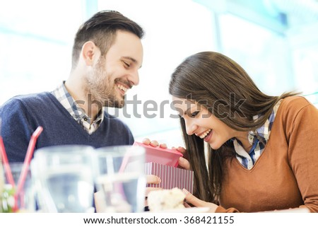 Shot of a young man surprising her girlfriend with a gift