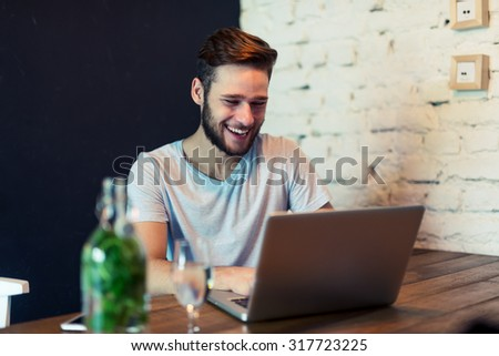 Shot of a young man working on a laptop in a cafe. Selective focus, natural light, higher ISO, grainy image. - stock photo