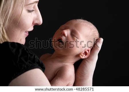 Shot of a Young Mother Smiling whilst Holding her Newborn Child