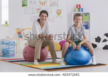Shot of a young woman and a little boy sitting on exercise balls in a room