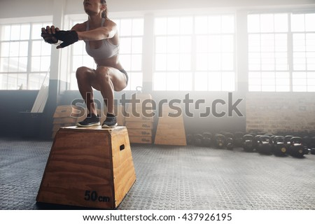 Shot of a young woman jumping onto a box as part of exercise routine. Fitness woman doing box jump workout at crossfit gym. - stock photo