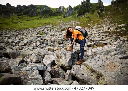 Shot of a young woman looking at the landscape while hiking in the mountains. Young happy woman hiker tying boot laces on rock, high in the mountains. Trekking Shoes