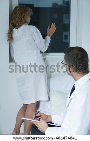 Shot of a young woman looking through the window and her psychiatrist observing her