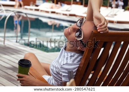 Shot of a young woman with morning coffee relaxing outdoors while on vacation. Beautiful woman, relaxing beside a luxury swimming pool. Girl at travel spa resort pool. (focus on woman face) - stock photo