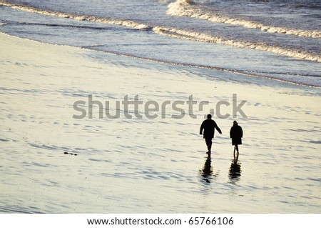 Shot of adult couple walking on the beach of Saint-Malo in brittany, france - stock photo