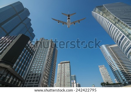 Shot of airplane flying above skyscrapers in City of Bangkok downtown - stock photo