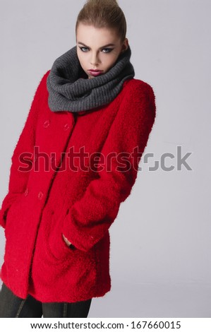 Shot of an attractive fashionable girl in coat posing in studio. - stock photo