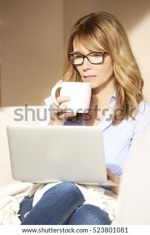 Shot of an attractive middle aged woman using her laptop and drinking tea while sitting on couch at home.
