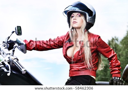 Shot of an attractive woman biker posing near her motorcycle. - stock photo