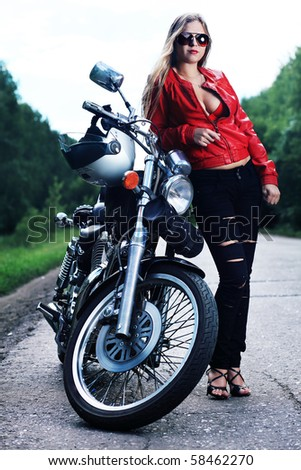 Shot of an attractive woman biker posing on her motorcycle. - stock photo