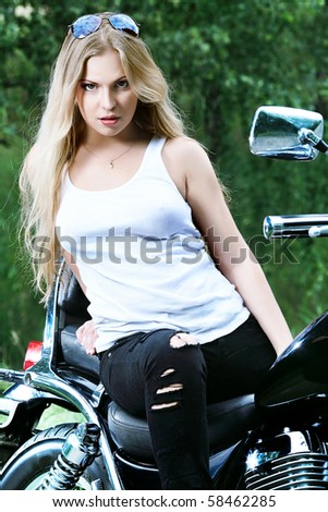 Shot of an attractive woman biker posing on her motorcycle.