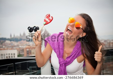 Shot of an attractive young woman eating a Barcelona lollipop. Beautiful girl enjoying summer day, smiling laughing looking at camera. - stock photo