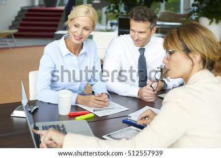 Shot of an executive businesswoman sitting in front of computer and presenting the new business ideas to her team.