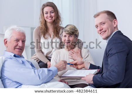 Shot of an old man on a hospital bed surrounded by his family smiling at the camera